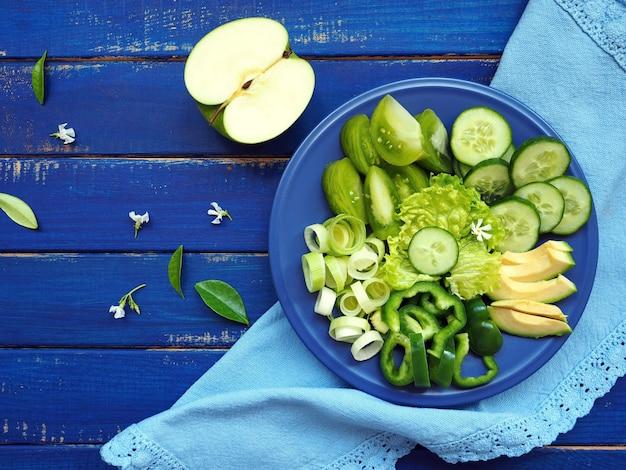 Frutta e verdura verdi - porro, cetriolo, insalata di lattuga, avocado, mela e pepe verde sulla tavola di legno blu