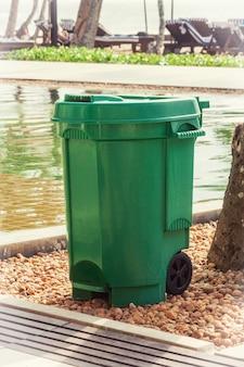 Cestino della spazzatura verde vicino al primo piano estremo della piscina.
