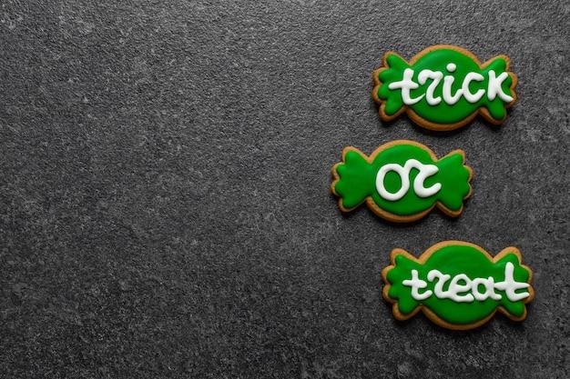 Biscotti verdi del pan di zenzero di halloween sotto forma di caramella con il portafoglio dell'iscrizione o lo spazio della copia di vita