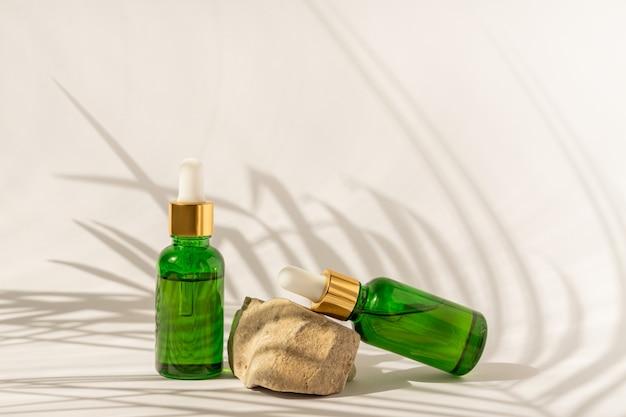 Flaconi per la cosmetica in vetro verde con contagocce su una superficie beige con pietre e foglie tropicali