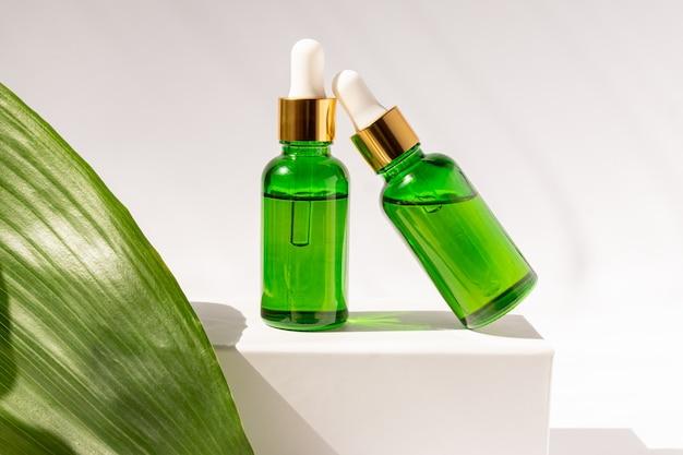 Flaconi per la cosmetica in vetro verde con un contagocce su un podio bianco con foglie tropicali