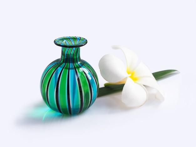 Vaso di vetro verde con la fioritura e le foglie bianche del fiore della stazione termale di plumeria isolate.