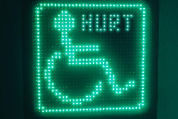 Simbolo luminoso verde dei disabili appeso al muro
