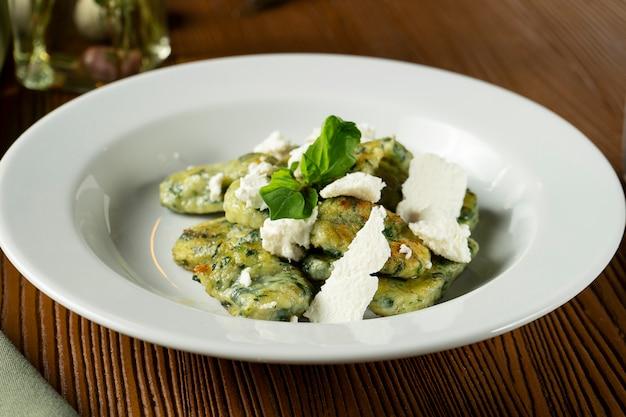 Gnocchi verdi con basilico, spinaci, pesto di feta in composizione con panno verde e olio d'oliva. Foto Premium