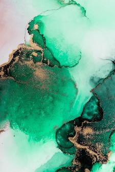 Fondo astratto dell'oro verde della pittura di arte dell'inchiostro liquido di marmo su carta.