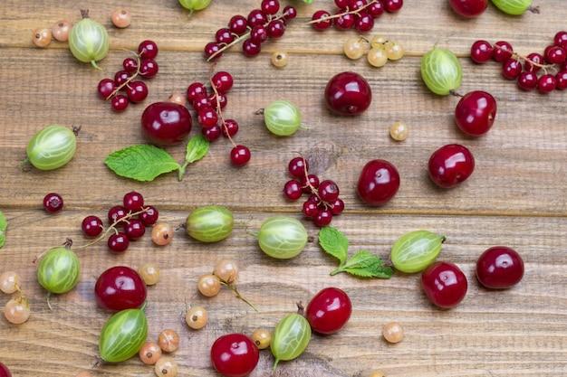 Ribes verde, ciliegie e foglie di menta sul tavolo. fondo in legno. lay piatto