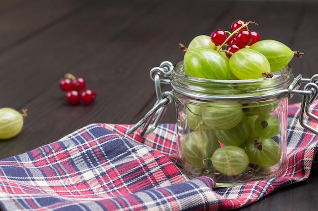 Ribes verde in barattolo di vetro e sul tovagliolo. ribes rosso. vista dall'alto. fondo in legno.
