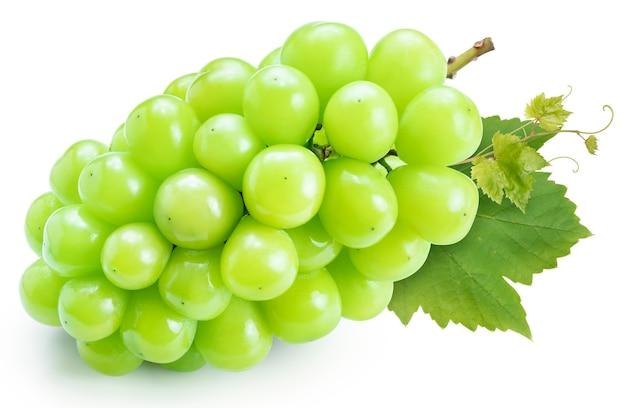 Uva verde con foglie isolate su bianco