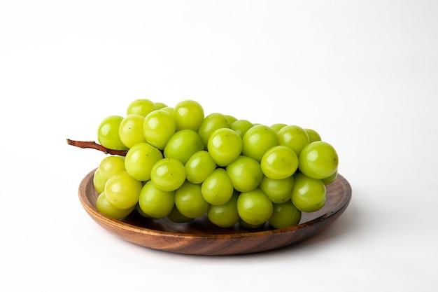 Uva verde su un piatto di legno