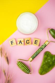 Strumenti di massaggio facciale verde gua sha. rullo realizzato in giada di quarzo verde su fondo rosa-giallo. vasetto di crema, faccia di iscrizione in lettere di legno. primo piano, vista dall'alto.