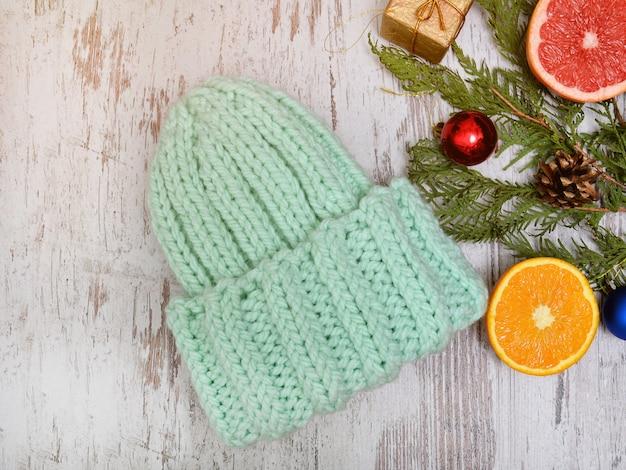 Cappello verde, agrumi e addobbi per l'albero di natale