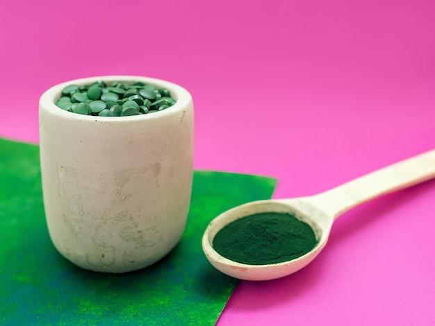 Spirulina hawaiana verde in cucchiai di pillole e polvere su sfondo rosa
