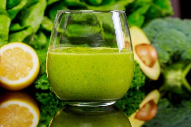 Frullato sano verde con broccoli, limone e avocado a fuoco sfocato.