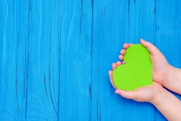 Cuore verde nelle mani del bambino
