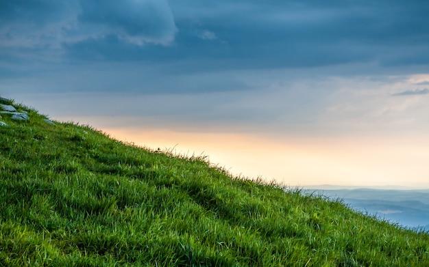 Collina verde al bel tramonto in montagna