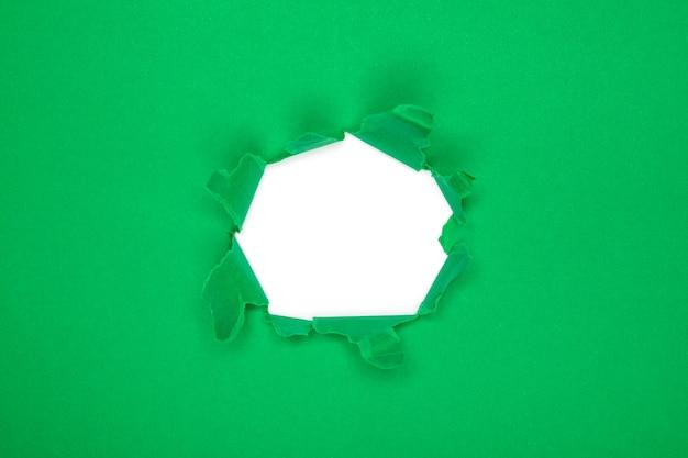 Buco verde nella carta con i lati strappati