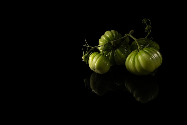 Bei pomodori fatti in casa verdi su sfondo nero