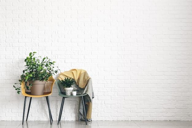 Piante d'appartamento verdi sulle sedie vicino al muro di mattoni bianchi