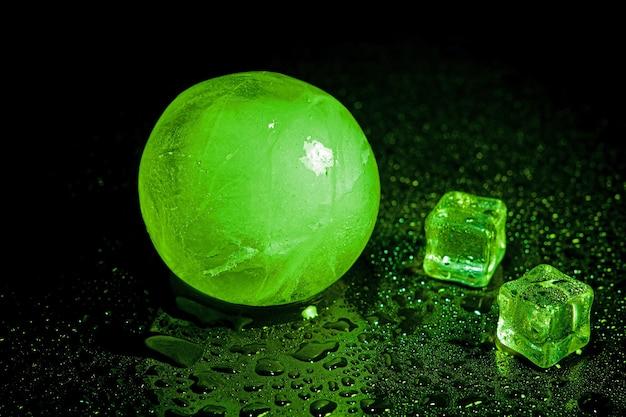 Riflessione verde della palla di ghiaccio su sfondo nero.