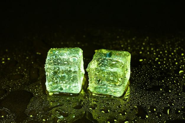 Cubetti di ghiaccio verdi sul tavolo nero.