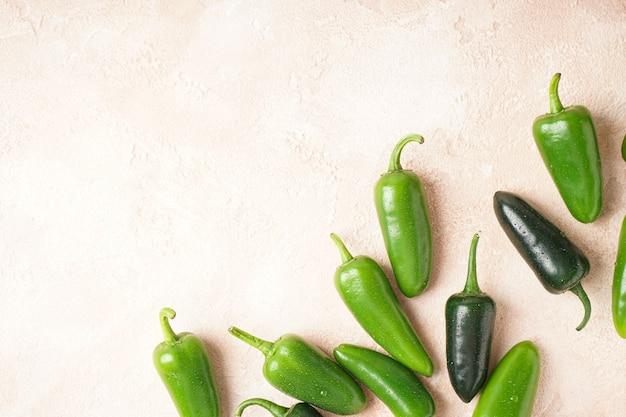 Fondo beige dei peperoni verdi del jalapeno, posto per testo. vista dall'alto.
