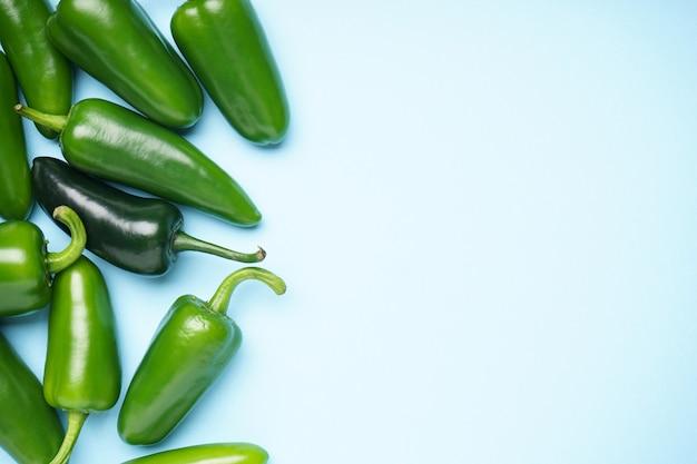 Fondo blu dei peperoni verdi del jalapeno, posto per testo. disposizione piatta.