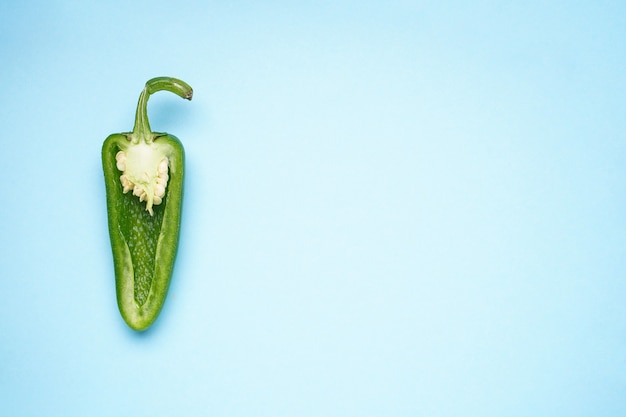 Fondo blu dei peperoni verdi del jalapeno, posto per testo. vista dall'alto.