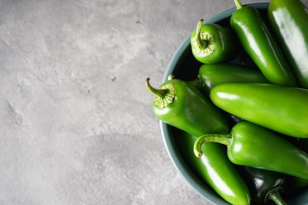 Peperoni verdi del jalapeno in un piatto su un fondo grigio, posto per testo, primo piano.