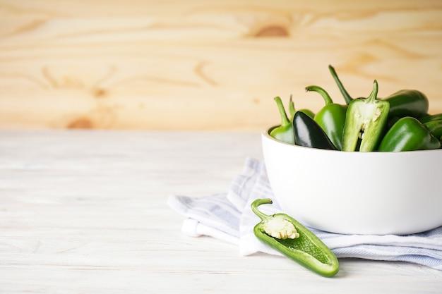 Peperoni jalapeno verdi in un piatto bianco su uno sfondo di legno, spazio per il testo.