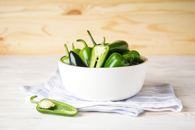 Peperoni jalapeno verdi in un piatto di legno bianco su uno sfondo di legno.