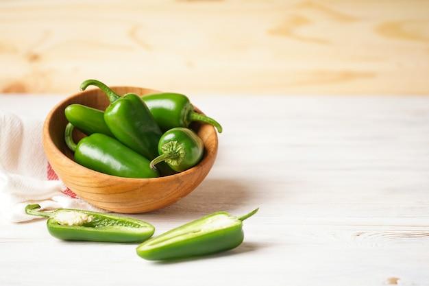Peperoni jalapeno verdi in un piatto di legno su uno sfondo di legno, spazio per il testo.