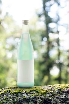 Succo verde in una bottiglia di vetro limonata di agave nella foresta acqua gassata agrodolce con in...
