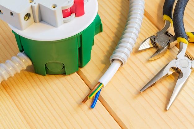 Scatola di giunzione verde con filo e strumenti per la riparazione di componenti elettrici in casa su tavole di legno
