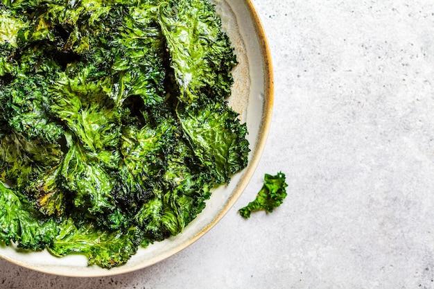 Chips di cavolo verde con sale in un piatto bianco, vista dall'alto. concetto di cibo vegano sano.