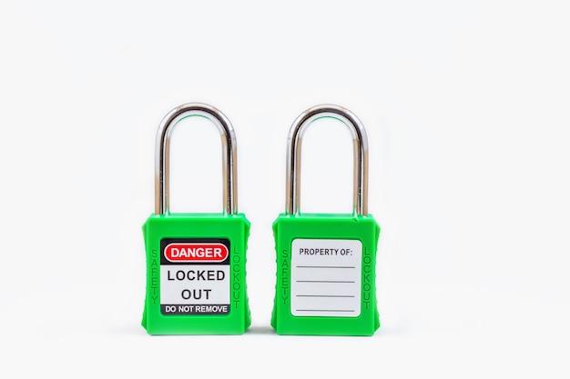 Blocco con chiave verde e tag per interruzione del processo elettrico, il numero di tag di attivazione / disattivazione per il tag di disconnessione elettrica su uno spazio bianco