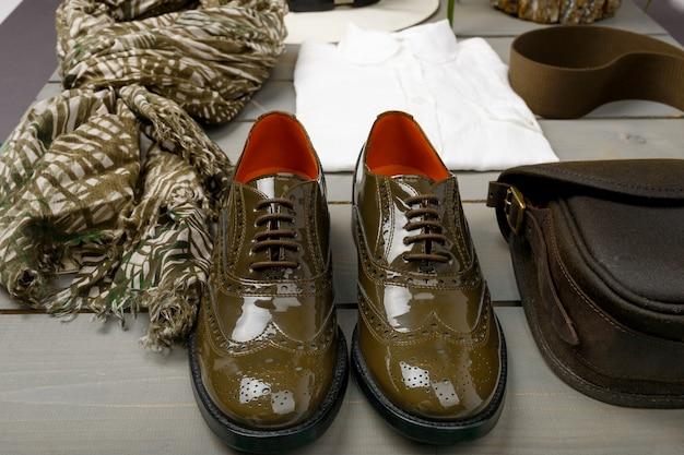 Scarpe oxford laccate verdi vicino alla camicia, alla borsa e alla sciarpa bianche su fondo di legno. vista posteriore.