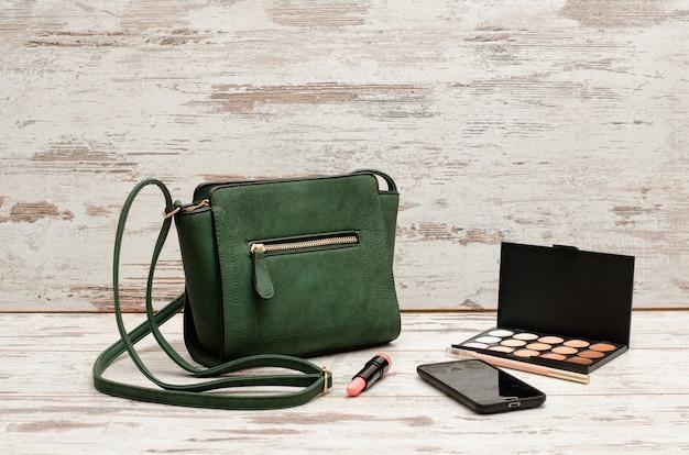 Borsa da donna verde, telefono, tavolozza di ombretti e un rossetto su uno sfondo di legno. concetto di moda