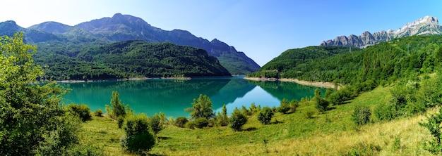 Paesaggio verde con lago e alte montagne che si riflettono nell'acqua, nel cielo blu e nel chiarore del sole. vista panoramica. pirenei, aragona, spagna. europa.