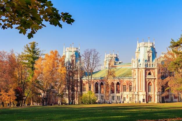Prato verde di fronte al grand palace nel parco tsaritsyno a mosca su uno sfondo di alberi con foglie colorate alla soleggiata giornata autunnale
