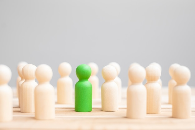 Uomo d'affari leader verde con folla di gente di legno. leadership, affari, squadra, lavoro di squadra e concetto di gestione delle risorse umane