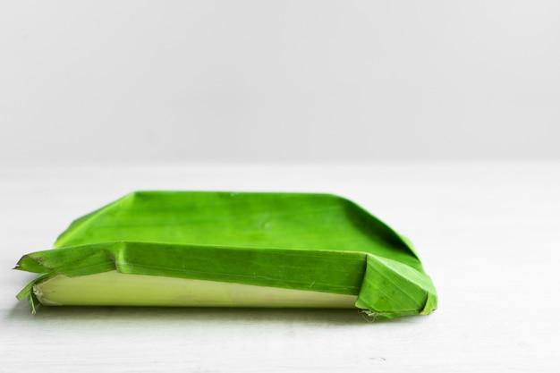 Foglia verde di una banana. piatti ecologici per alimenti. cornice di cartone avvolta in una foglia di banana. piatto ecologico