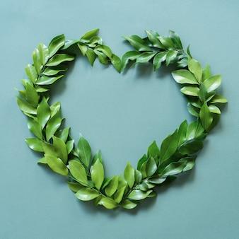 Le foglie verdi sono disposte a forma di cuore con uno sfondo verde brillante e blu