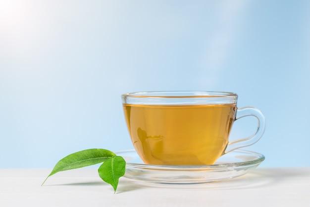 Foglie verdi e un bicchiere tazza di tè su un tavolo bianco. una bevanda tonificante utile per la salute.