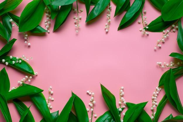 Foglie verdi di mughetto come cornice floreale con spazio copia piatto con sfondo rosa pink