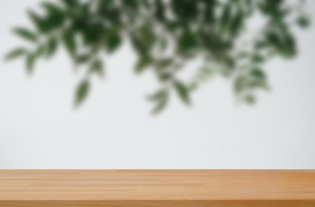 Foglie verdi su sfondo bianco con espositore da tavolo in legno liscio