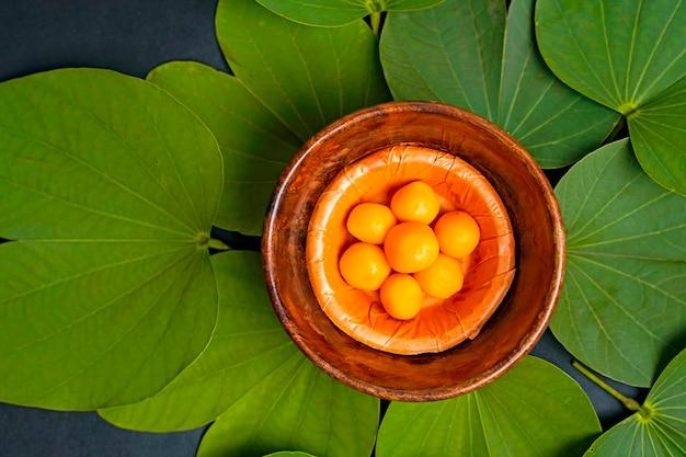 Foglie verdi con dolci in una ciotola di legno