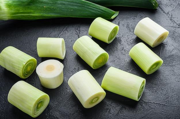 Porri verdi oninon sultano crudo con ingredienti di erbe, su fondo nero
