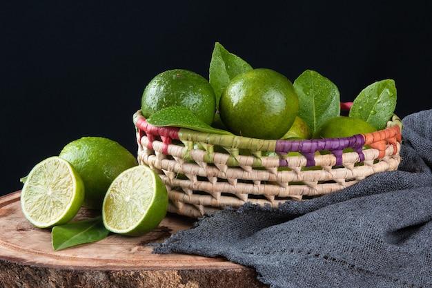 Cestino di frutta al limone verde con superficie nera.