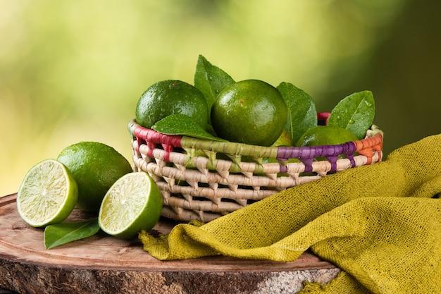 Merce nel carrello della frutta del limone verde con superficie verde vaga.