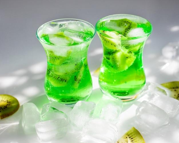 Limonata verde con fette di kiwi e ghiaccio. due bicchieri di vetro stanno sul tavolo.